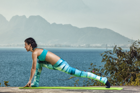 Beautiful young and fit woman exercising yoga at the mediterranean sea in Antalya. Sea and mountains in the background. Stock Photo