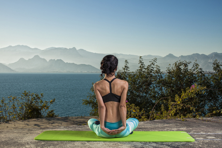 feminine: Beautiful young and fit woman exercising yoga at the mediterranean sea in Antalya. Sea and mountains in the background. Stock Photo