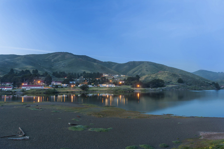 This image was taken at Rodeo Beach located in the Marin Headlands located near Sausalito, Ca. This image was captured just as the lights in the old military building were beginning to come on. Stock Photo