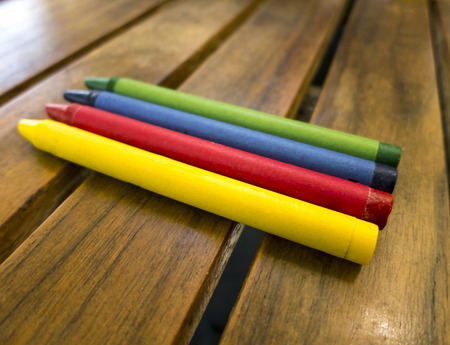 This is an image of a set of coloring crayons aranged on a wooden table.  They are aranged by primary colors.