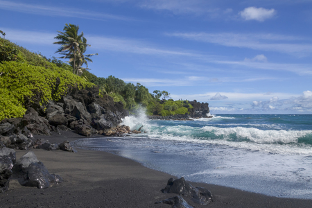 WaiÊ»anapanapa State Park located in the town of Hana, Hawaii feature beautiful volcanic black sand beaches and gorgeous coastline hiking trails that lead you spectacular views. Stock Photo