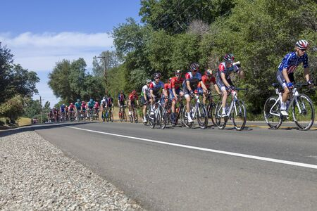 Amgen, Tour of California, SACRAMENTO, CA –May 13, 2019: Amgen, Tour of California race is on it's way to South Lake Tahoe, California during stage 2 from Rancor Cordova, California.  In the image the peloton is working it's way on Bass Lake Road in