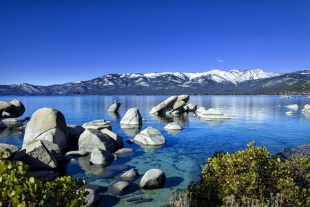 The image is of Sand Harbor, a Neveda State Park located on the Northeast shore of Lake Tahoe in the late winter with lingering snow throughout the park.