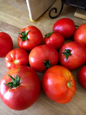 Table of Tomatoes, SAN FRANCISCO, CA –June 22, 2017: An image of tomatoes waiting to be cooked on a oak table in a San Francisco kitchen. These tomatoes were freshly picked from a local garden in the city. Banco de Imagens