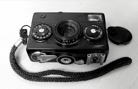 Black and White Camera, SAN JOSE, CA –January 1, 2019: A black and white image of an old 60's camera with a strap with lens cap positioned on the side.