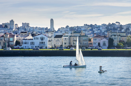 Sailing San Francisco Bay, SAN FRANCISCO, CA - DECEMBER 10, 2017: The image is of a small sail boat taking a trip in front San Francisco�s Marina district. Sailing is a popular activity with San Francisco tourists and residents sailing boats of all size