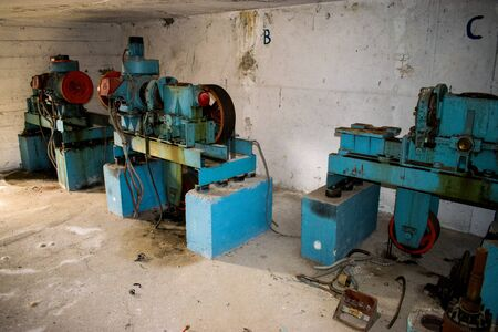 Three old elevator motors in a concrete lift room