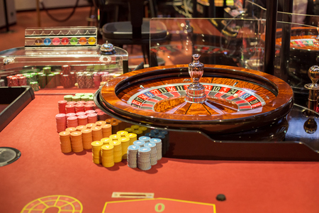 Roulette wheel in Casino with chips. Casino background.