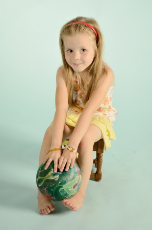 nice young girl sitting on a chair with ball on blue background