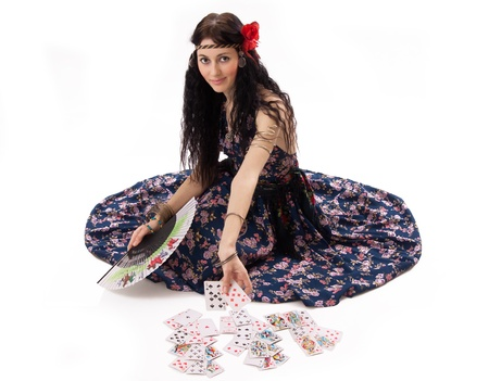 gypsy woman: young gypsy tells fortunes by playing cards  Stock Photo
