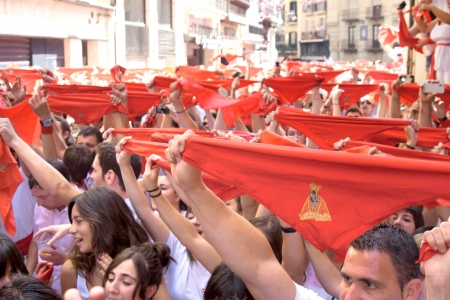 hemingway: PAMPLONA, SPAIN -JULY 6: People welcome the opening of the San Fermin festival in the street Curia. Pamplona, Navarra, Spain 6 July 2011 in Pamplona Spain. Noon