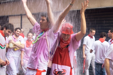 PAMPLONA, SPAIN -JULY 6: Young people having fun at the opening of the San Fermin festival in the street Curia. . Pamplona, Navarra, Spain 6 July 2011 in Pamplona Spain. Noon