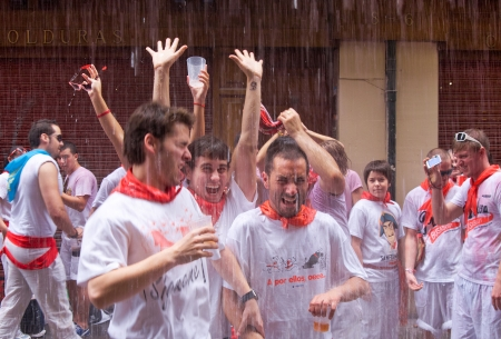 hemingway: PAMPLONA, SPAIN -JULY 6: Young people having fun at the opening of the San Fermin festival in the street Curia. . Pamplona, Navarra, Spain 6 July 2012 in Pamplona Spain. Noon