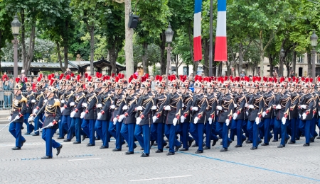 synchronously: PARIS - JULY 14: Army columns marching at a military parade in the Republic Day (Bastille Day) on the Champs Elysees in Paris, France on July 14, 2012 Editorial