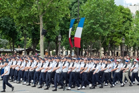 synchronously: PARIS - JULY 14: Army columns marching at a military parade in the Republic Day (Bastille Day) on the Champs Elysees in Paris, France on July 14, 2012. Editorial
