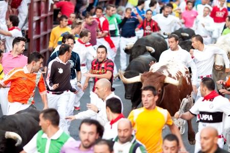 MADRID SUBURB OF SAN SEBASTIAN DE LOS REYES - SEPTEMBER 30   Men run from the bulls on the street of San Sebastian de los Reyes during festival, Spain 2013  Fiesta called  little Pamplona