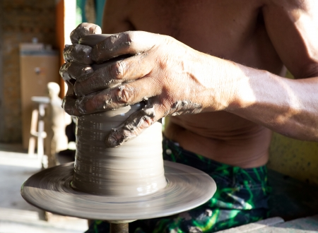 hands of a potter manufactures clay pot photo
