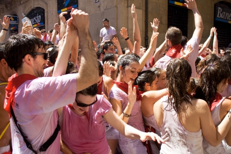 hemingway: PAMPLONA, SPAIN -JULY 6: Young people having fun at opening of San Fermin festival in street Curia. Pamplona, Navarra, Spain 6 July 2013 Editorial