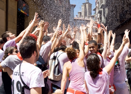 hemingway: PAMPLONA, SPAIN-JULY 6: People stand under the spray of water at opening of San Fermin festival. Plaza Consistorial in front of municipality. Pamplona, Navarra, Spain July 6, 2013
