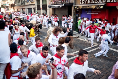 PAMPLONA, SPAIN -JULY 8: Unidentified men run from bulls in street Estafeta during San Fermin festival in Pamplona, Spain on July 8, 2013. Editorial