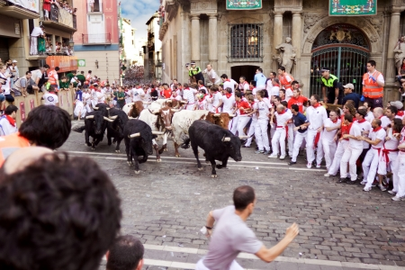 PAMPLONA, SPAIN-JULY 9: Bulls and people are running in street during San Fermin festival in Pamplona, Spain on July 9, 2013. Editorial