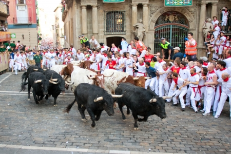 navarra: PAMPLONA, SPAIN-JULY 9: People run from bulls on street during San Fermin festival in Pamplona, Spain on July 9, 2013.. Editorial