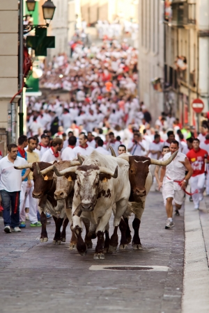 PAMPLONA, SPAIN-JULY 9: Bulls and men running in street during San Fermin festival in Pamplona, Spain on July 9, 2013.