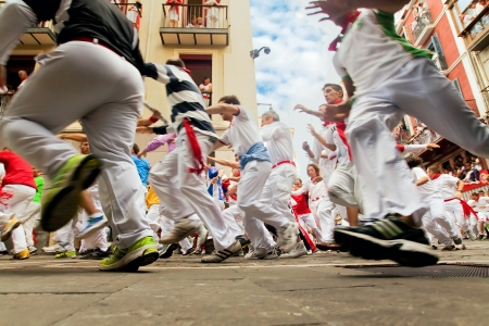 PAMPLONA, SPAIN-JULY 12: People run from bulls on street during San Fermin festival in Pamplona, Spain on July 12, 2013