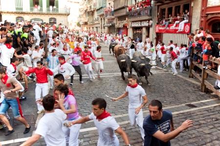 PAMPLONA, SPAIN -JULY 14: Unidentified men run from bulls in street Estafeta during San Fermin festival in Pamplona, Spain on July 14, 2013.