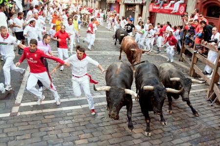 パンプローナ、スペイン-7 月 14 日: 2013 年 7 月 14 日にスペイン、パンプローナのサンフェルミン祭の間に通り Estafeta の雄牛から正体不明の男性を実行します。