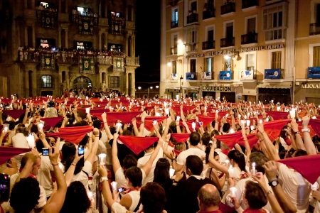 PAMPLONA, SPAIN-JULY 14: People with red handkerchiefs at closing of San Fermin festival. Plaza Consistorial in front of municipality. Pamplona, Navarra, Spain July 14, 2013