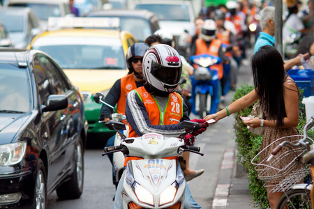 BANGKOK - FEBRUARY 28: A woman pays for the service motorcycle taxi on the street Bangkok Thailand, February 28, 2014. A common way of move the local people in Thailand.