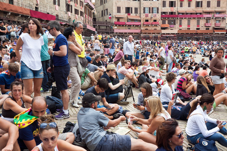 palio: SIENA ITALY AUGUST 16: Spectators in anticipation of start of annual traditional Palio di Siena horse race in medieval square quotPiazza del Campoquot August 16 2014 in Siena Italy Editorial