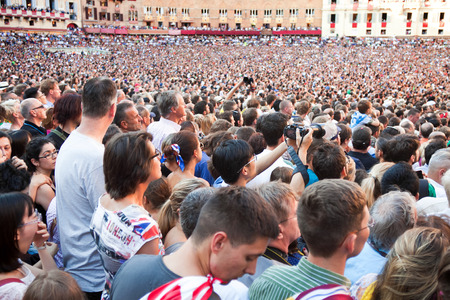 palio: SIENA, ITALY - AUGUST 16: Spectators смотрят of start of annual traditional Palio di Siena horse race in medieval square Piazza del Campo August 16, 2014 in Siena, Italy Editorial