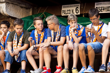 palio: SIENA, ITALY - AUGUST 15: Fans in pre-start of annual traditional Palio di Siena horse race in medieval square Piazza del Campo August 15, 2014 in Siena, Italy