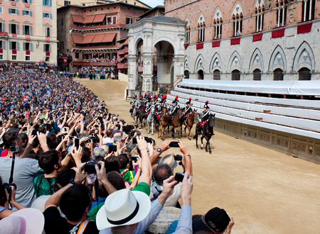 palio: SIENA, ITALY - AUGUST 16: Performance of cavalry on parade before start of annual traditional Palio di Siena horse race in medieval square Piazza del Campo August 16, 2014 in Siena, Italy