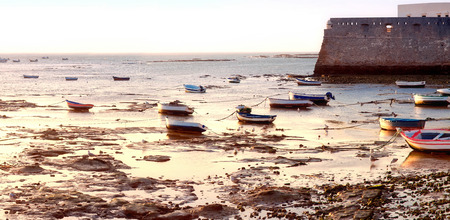 forefront: wall castle of Santa Catalina with aged ships on forefront, Cadiz, Andalusia, Spain Stock Photo