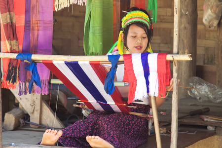 flee: BAN NAI SOI, MAE HONG SON PROVINCE, THAILAND - FEBRUARY 6: Karen tribe woman working at loom in Ban Nai Soi, Thailand, February 6, 2014. Repression Karen in Myanmar forced them to flee to Thailand