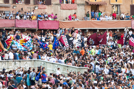 historic world event: SIENA, ITALY - AUGUST 16: Spectators in anticipation of start of annual traditional Palio di Siena horse race in medieval square Piazza del Campo August 16, 2014 in Siena, Italy