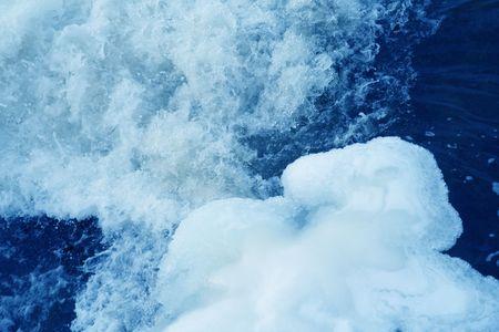 snow scene with rushing water hitting ice berg photo