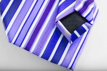 navy blue background: closeup of navy blue and purple stripe business tie on white background Stock Photo