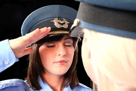 alternate angle of beautiful brunette and blonde female police officers facing each other saluting Stock Photo