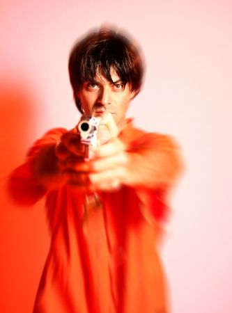 escaped: escaped prisoner with prison clothes pointing a gun Stock Photo