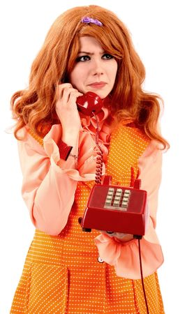 carroty: woman in an orange dress on a red phone with sixties 60s orange everywhere Stock Photo