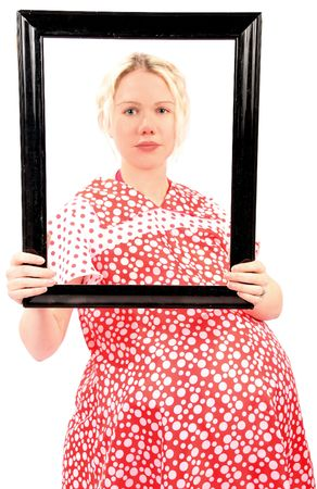 blond pregnant woman in a red dress holding a black frame photo