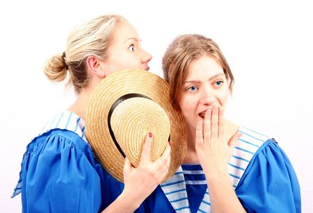 beautiful blond sisters in classic blue swim wear who are sisters whispering a shocking secret to one another behind a straw thatched hat Zdjęcie Seryjne