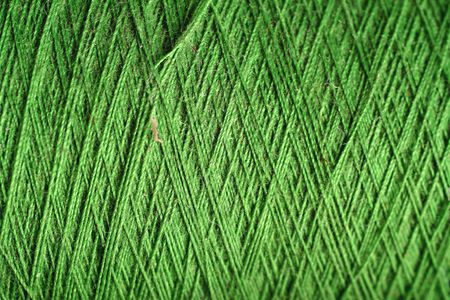 green thread fabric wool yarn wrapped in a spool of threads and textiles great for a background Zdjęcie Seryjne