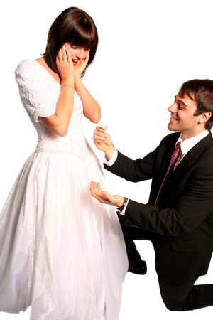 request: handsome groom with a proposal for marriage and a beautiful shocked bride in her bridal dress looking at the wedding ring