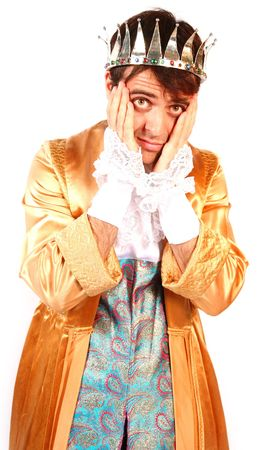 discredit: shy attractive young man prince with face in hands in shame and fear dressed in golden robes