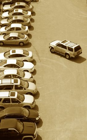 space area: one more parking space left in a crowded stuffed lot of cars in the urban city setting Stock Photo